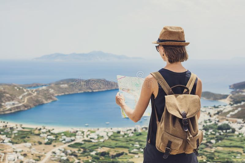 Woman traveler with backpack holding map. Travel, tourism, summer holidays, active lifestyle concept. Hipster tourist girl looking stock images