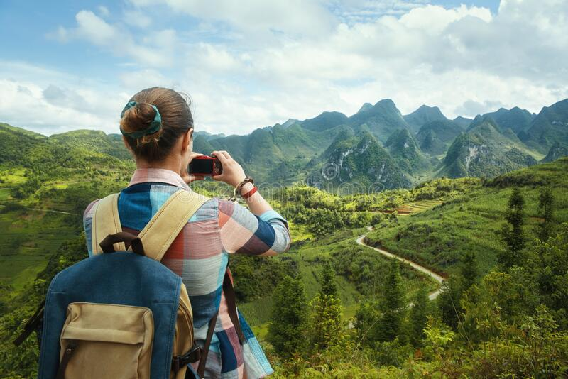 Woman Traveler with backpack, photographs beautiful view of the karsts mountains in the North of Vietnam. royalty free stock image