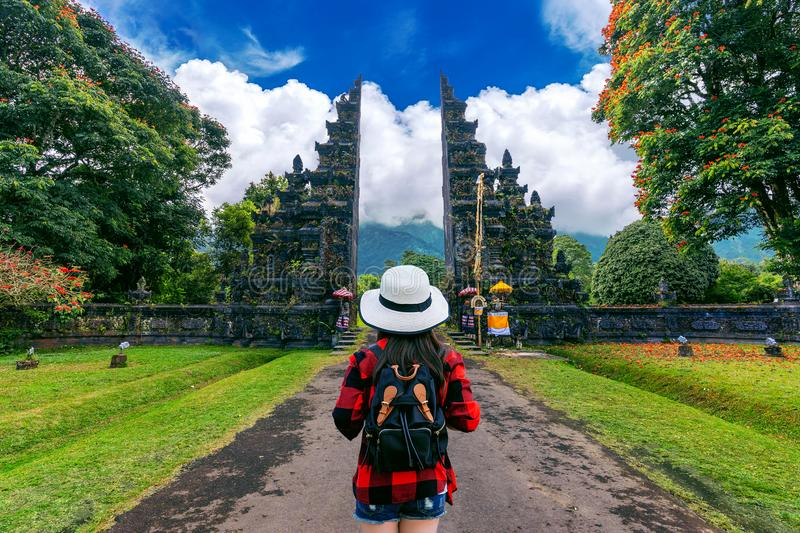 Woman traveler with backpack walking at Big entrance gate in Bali, Indonesia. stock images