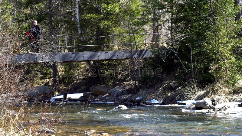 Woman traveler is on bridge over mountain river in spring. Media. Traveler crosses iron bridge over mountain river royalty free stock images