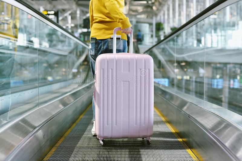 Woman traveler carry big suitcase on escalator walkway at the airport terminal. royalty free stock photography