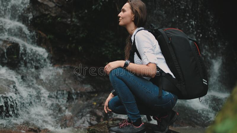 Woman traveler crouch near splashing waterfall royalty free stock image