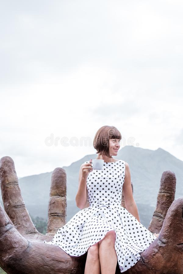 Woman traveler with cup of hot coffee on a mountain background. Volcano Batur, Bali island. Indonesia. Asia stock photo