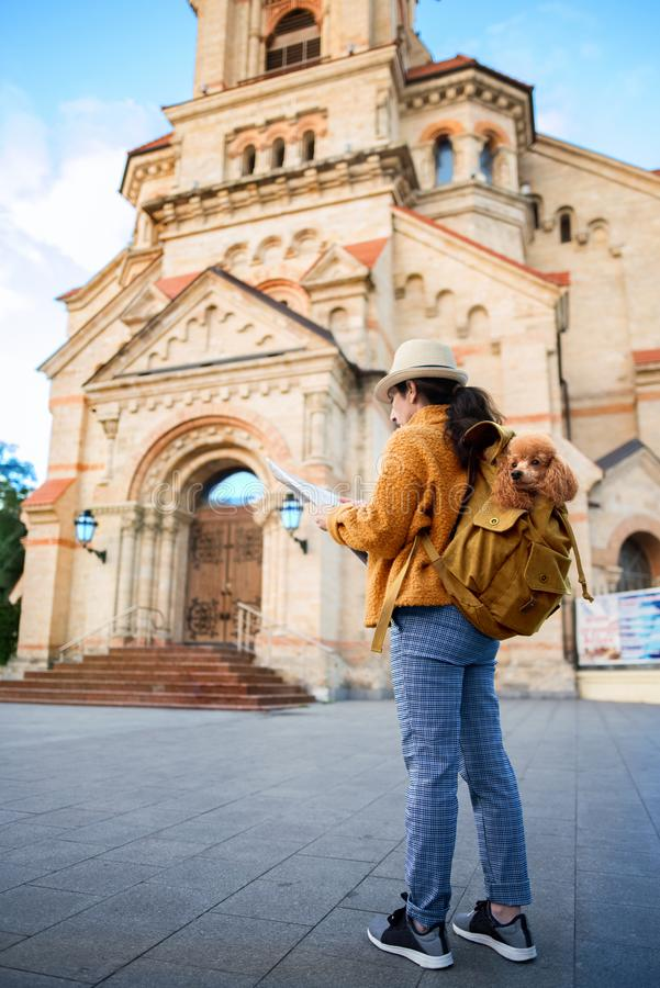 Woman traveler with dog in the backpack examines architectural monument . Concept of travel stock photography