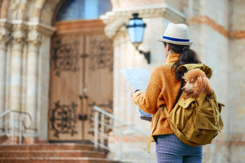 Woman traveler with dog in the backpack examines architectural monument . Concept of travel stock photo