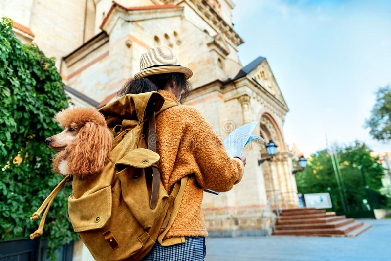 Woman traveler with dog in the backpack examines architectural monument . Concept of travel royalty free stock photos
