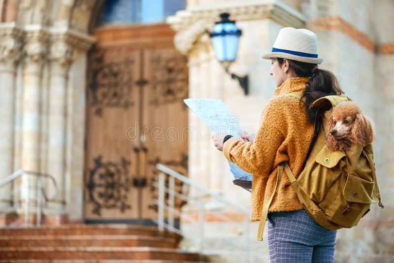 Woman traveler with dog in the backpack examines architectural monument . Concept of travel royalty free stock image