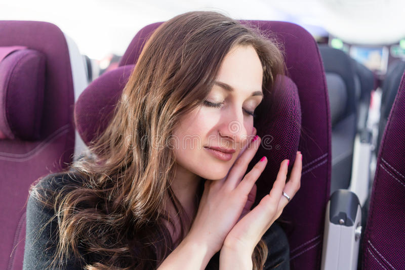 Woman traveler having nap in airplane cabin travelling to vacation. Woman traveler having a nap in airplane cabin travelling to her vacation stock photography