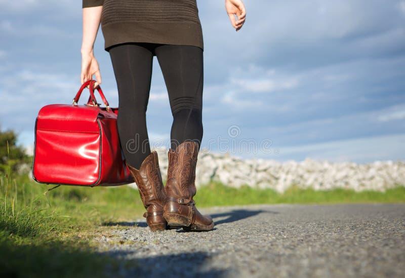 Woman traveler holding red bag stock image