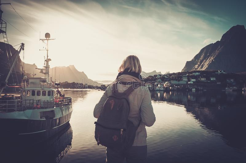 Woman traveler looking at sunset in Reine village, Norway royalty free stock photography