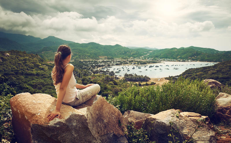 Woman traveler looks at the edge of the cliff on the sea bay of royalty free stock photo