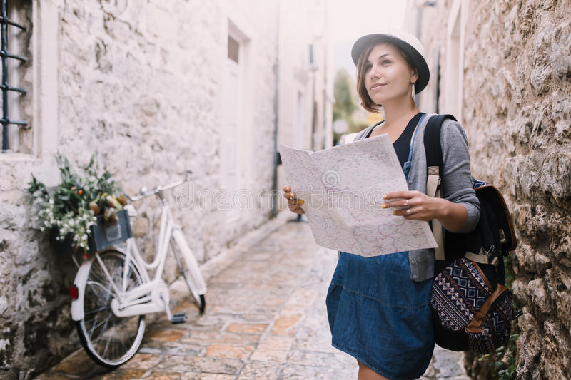 Woman traveler with map in old town Budva near vintage bicycle stock image