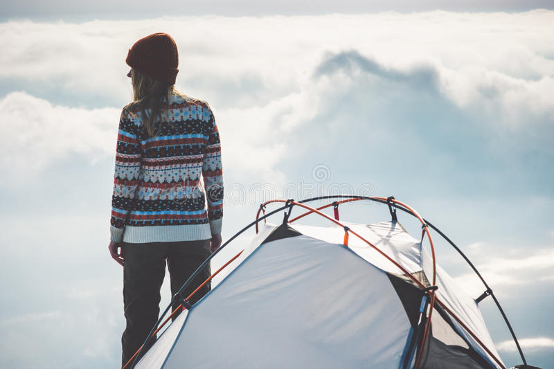 Woman Traveler on mountain summit and tent camping. Foggy clouds landscape on background Travel Lifestyle concept adventure vacations outdoor stock images