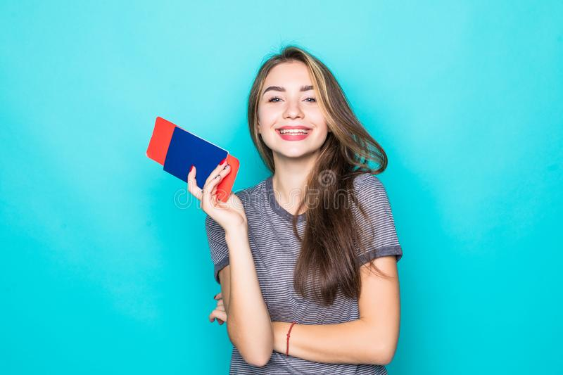 Young Woman traveler with passport and ticket on blue background. Woman traveler with passport and ticket on blue background royalty free stock photography
