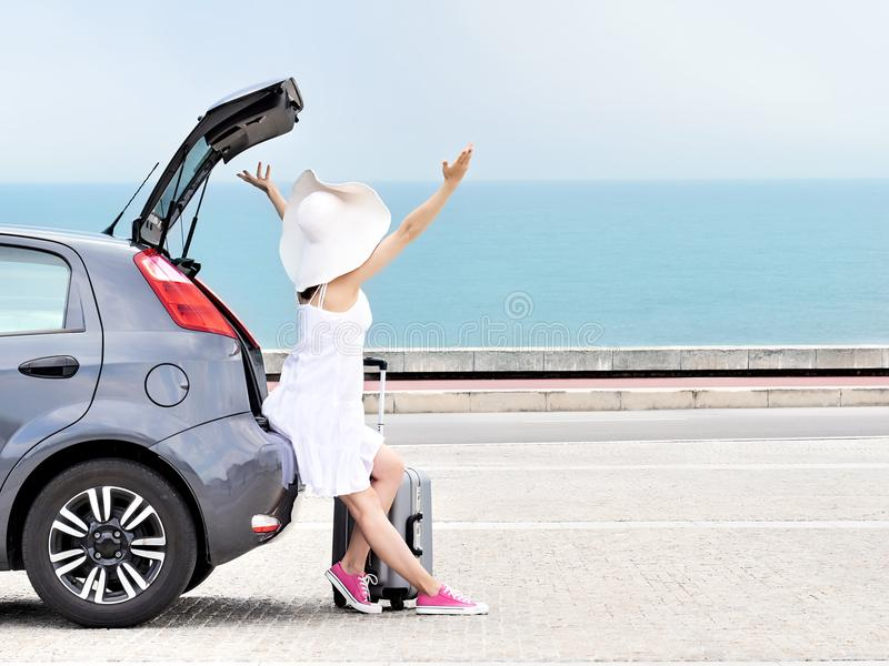 Woman traveler with raised arms on hatchback car on beach stock photos