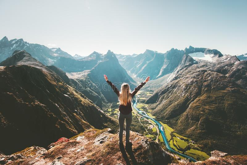 Woman traveler raised arms standing alone on cliff royalty free stock photo