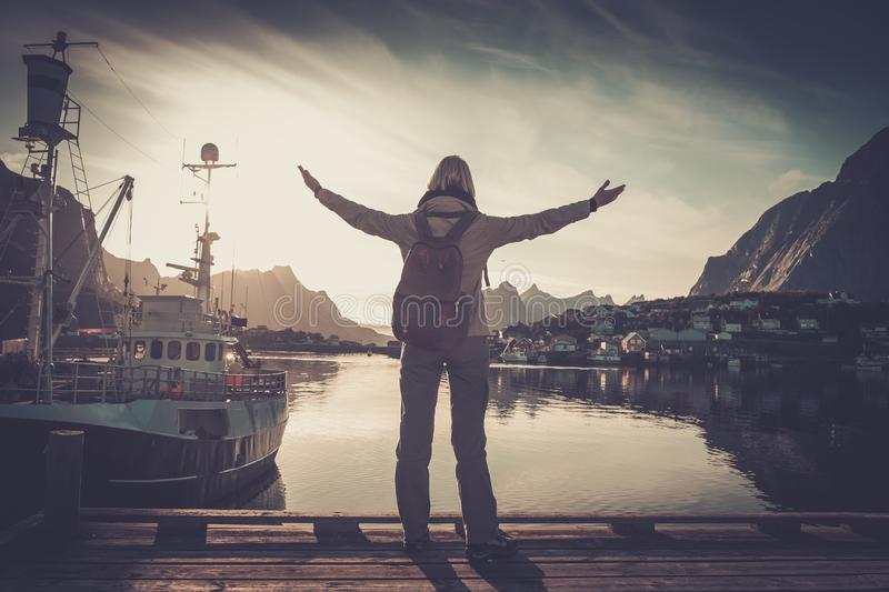 Woman traveler in Reine village with arms wide open royalty free stock photo