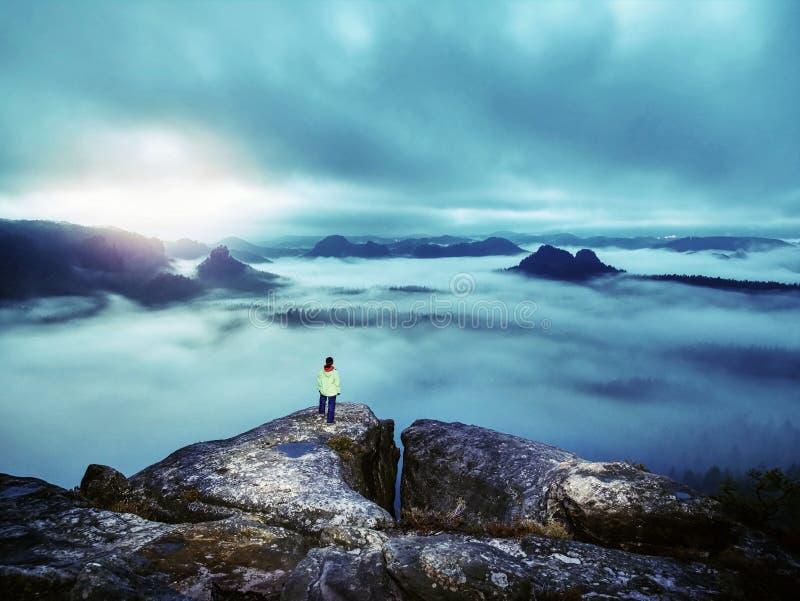 Woman traveler on rocky mountain and dark misty sky royalty free stock photos