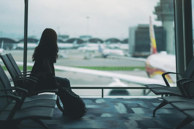 Woman traveler sitting and waiting with backpack at the airport stock photo