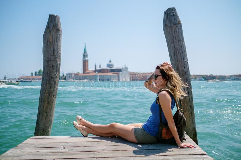 Woman traveler sitting on the wooden pier with Saint George island on the background. royalty free stock photography