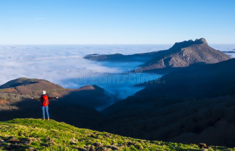 Woman traveler standing on mountain summit over clouds enjoying aerial view. Travel Lifestyle success concept adventure active vac stock photo