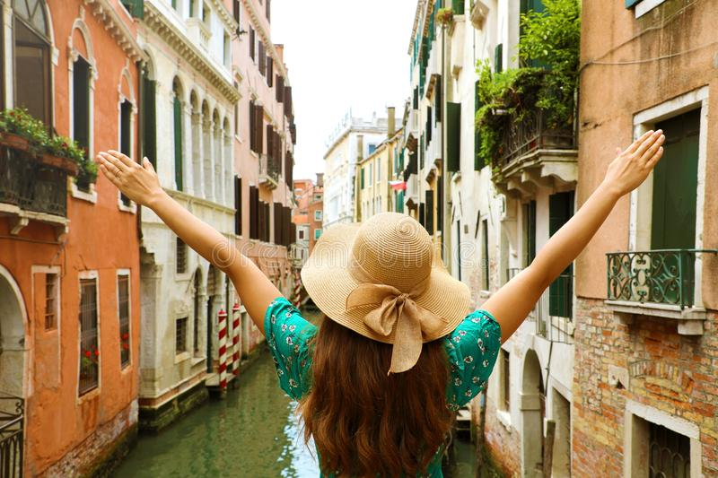 Woman traveler with straw hat and arms raised on bridge in Venice. Back view of fashion woman with open arms beautiful Venice stock photos
