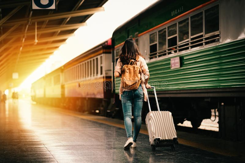 Woman traveler tourist walking with luggage at train station royalty free stock images