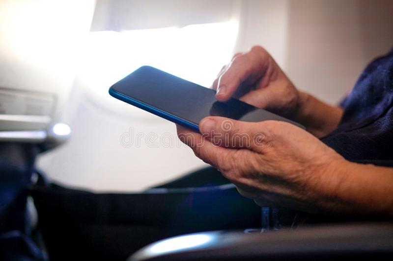 Woman traveler using smartphone in airplane. passenger holding mobile phone in aircraft. travel & connection. Woman traveler using smartphone in airplane stock images