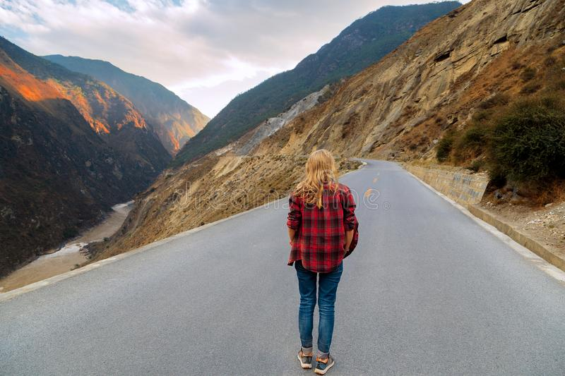 A woman traveler is walking along the road royalty free stock photography