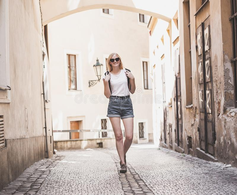 Woman traveler walking through arcade in european historic city. Hipster girl traveling in Europe. royalty free stock photos