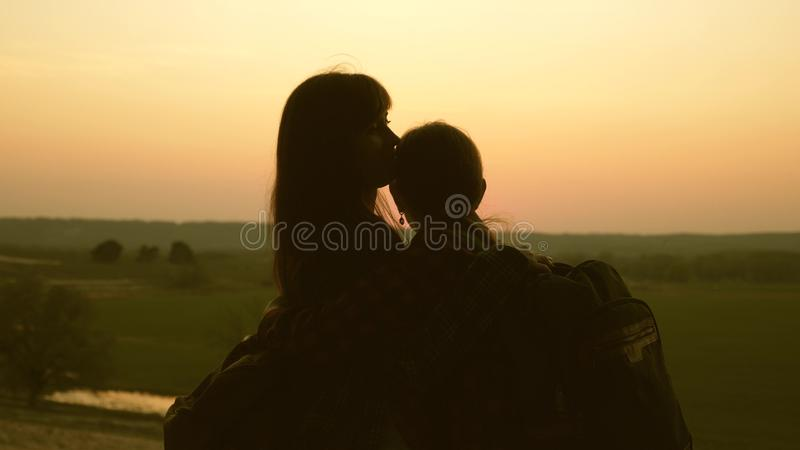 Woman travelers mom and daughter hug and enjoy their victory and enjoy the sunset. Hiker Girl. Teamwork travelers with. Backpacks. Family of tourists on royalty free stock image