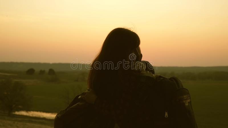 Woman travelers mom and daughter hug and enjoy their victory and enjoy the sunset. Hiker Girl. Teamwork travelers with. Backpacks. Family of tourists on royalty free stock photos