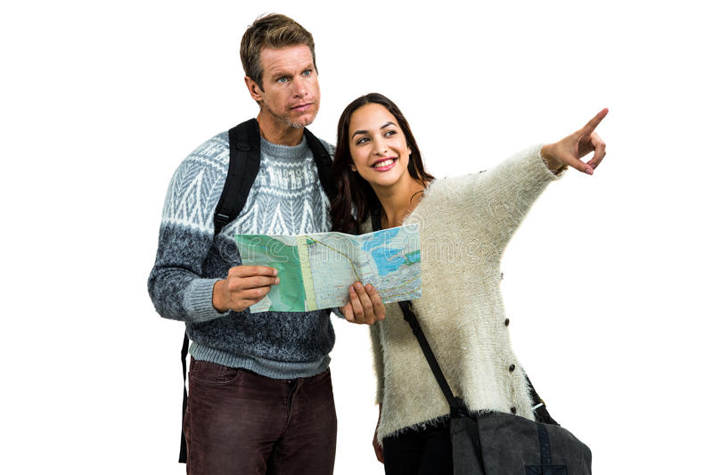 Woman traveling with boyfriend pointing while holding map. Woman traveling with boyfriend pointing against white background while holding map stock image