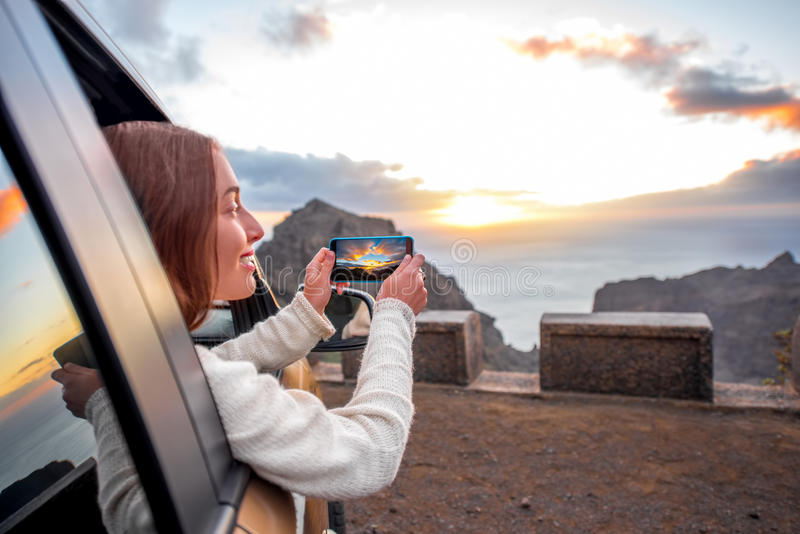 Woman traveling by car on La Gomera island. Young female traveler photographing with smartphone beautiful rocky coast on the sunset. Woman enjoying sunset royalty free stock image
