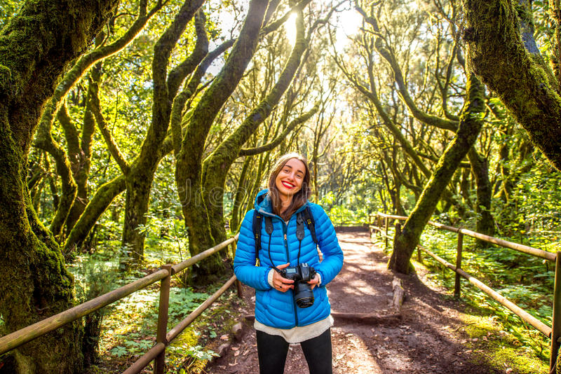 Woman traveling evergreen forest. Young woman in blue jacket traveling with backpack and photo camera in beautiful evergreen forest in Garajonay park on La royalty free stock photos
