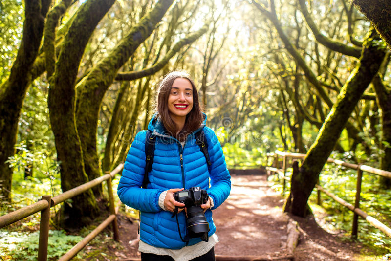 Woman traveling evergreen forest. Young woman in blue jacket traveling with backpack and photo camera in beautiful evergreen forest in Garajonay park on La royalty free stock images