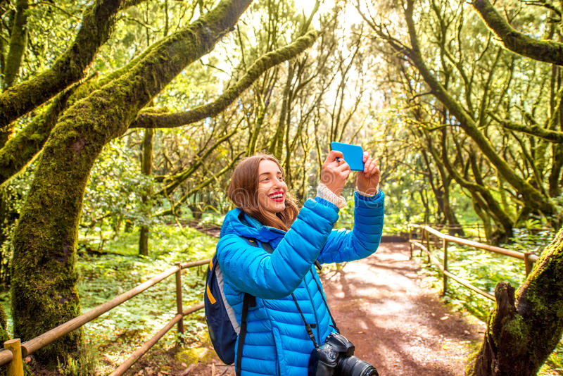 Woman traveling evergreen forest. Young woman in blue jacket traveling with backpack, photographing with smart phone beautiful evergreen forest in Garajonay park stock photo