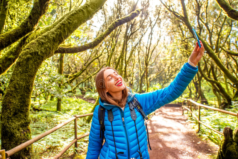 Woman traveling evergreen forest. Young woman in blue jacket traveling with backpack, photographing with smart phone beautiful evergreen forest in Garajonay park stock photos