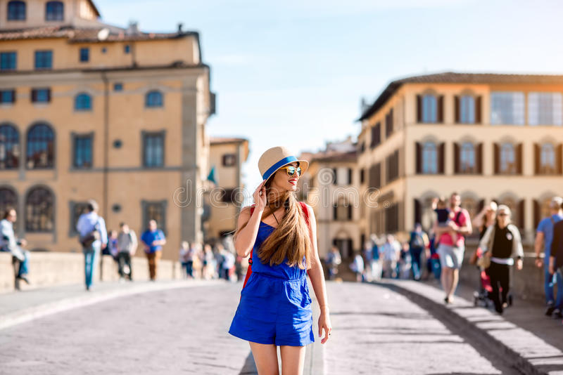 Woman traveling in Florence city. Beautiful female traveler in blue dress, hat and backpack walking on crowded Holy Trinity bridge in Florence city. Vacation in royalty free stock photo