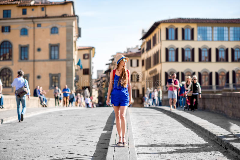 Woman traveling in Florence city. Beautiful female traveler in blue dress, hat and backpack walking on crowded Holy Trinity bridge in Florence city. Vacation in stock photo