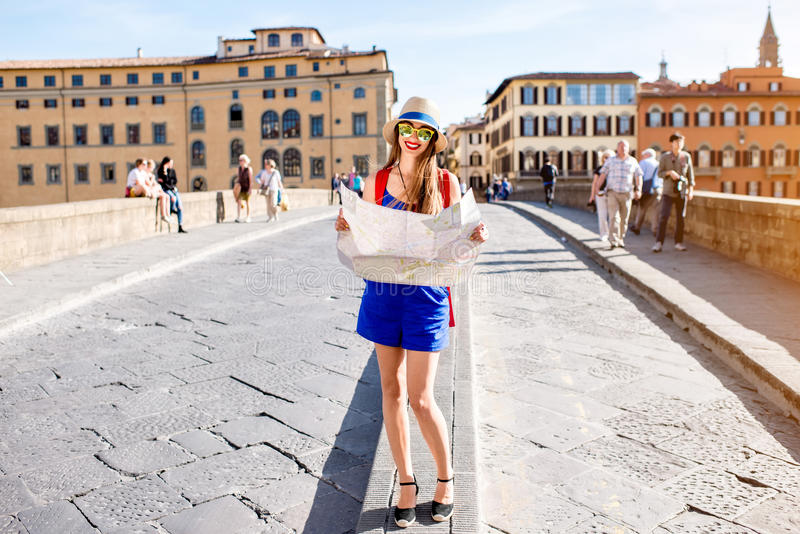 Woman traveling in Florence city. Young female traveler standing with paper map on the crowded bridge in Florence. Vacation in Italy stock image