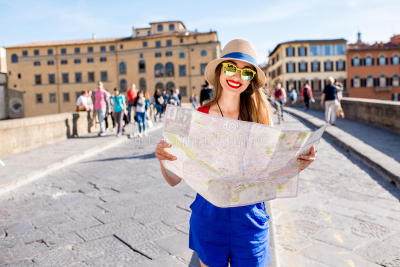 Woman traveling in Florence city. Young female traveler standing with paper map on the crowded bridge in Florence. Vacation in Italy royalty free stock photo
