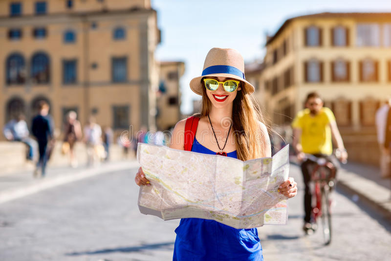 Woman traveling in Florence city. Young female traveler standing with paper map on the crowded bridge in Florence. Vacation in Italy stock photos