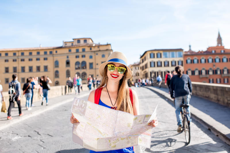 Woman traveling in Florence city. Young female traveler standing with paper map on the crowded bridge in Florence. Vacation in Italy stock photography