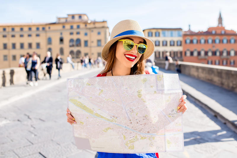 Woman traveling in Florence city. Young female traveler standing with paper map on the crowded bridge in Florence. Vacation in Italy royalty free stock images