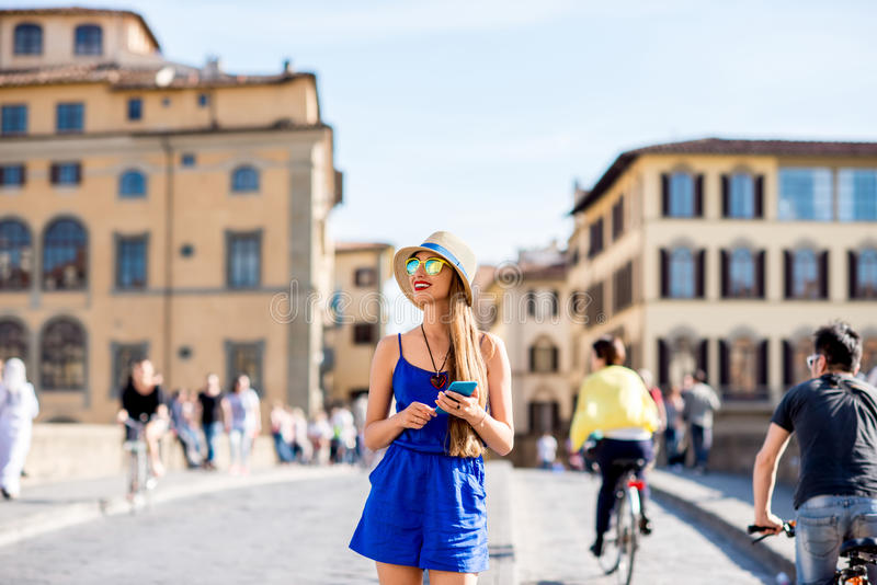 Woman traveling in Florence city. Young female traveler using mobile phone during the weekend in Florence royalty free stock images