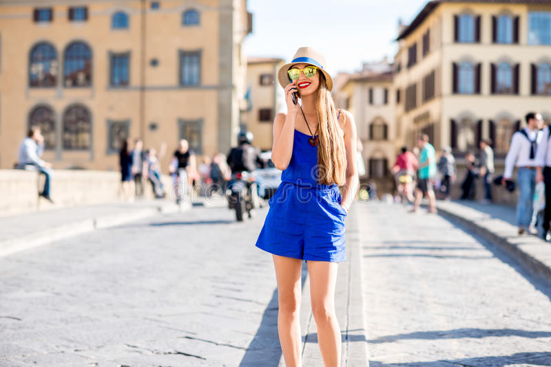 Woman traveling in Florence city. Young female traveler using mobile phone during the weekend in Florence royalty free stock image