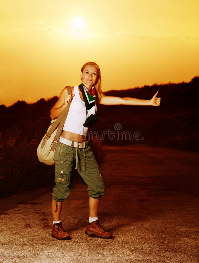 Woman traveling hitchhike. Image of active sporty girl traveling hitchhike, blond woman on road waiting for car, tourist female standing on highway with raised royalty free stock image