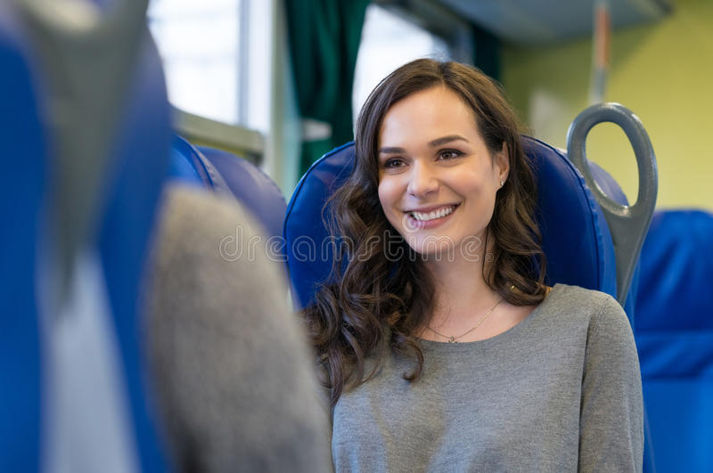 Woman traveling on the train. Portrait of a happy young women sitting in a train with blue seats. She's looking in front of her while she is travelling with her stock photography
