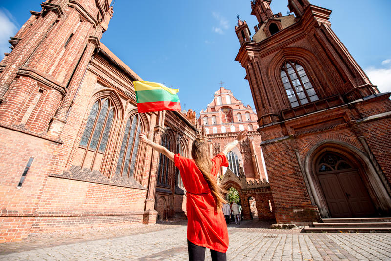 Woman traveling in Vilnius. Young female tourist with photo camera and lithuanian flag standing back near the famous gothic church in the old town of Vilnius royalty free stock image